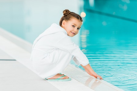 cheerful kid in bathrobe touching water in swimming pool Stok Fotoğraf - 118561479