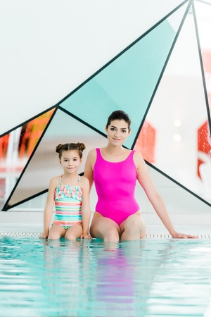 attractive mother sitting with daughter in swimwear and looking at camera near swimming pool