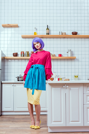 beautiful housewife with purple hair and colorful clothes posing in kitchen
