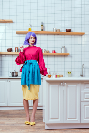 beautiful housewife with purple hair and colorful clothes posing in kitchen with copy space