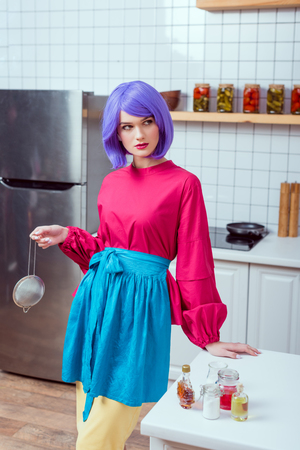 beautiful housewife with purple hair and colorful clothes holding sieve and posing in kitchen Reklamní fotografie