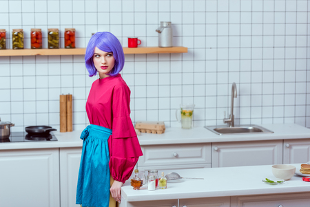 selective focus of beautiful housewife with purple hair and colorful clothes posing in kitchen with copy space Reklamní fotografie