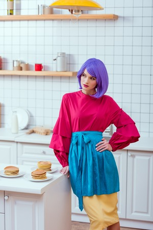 selective focus of housewife with purple hair and colorful clothes posing near kitchen counter with pancakes Reklamní fotografie