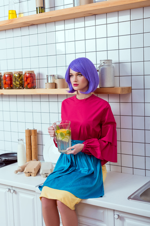 housewife with purple hair and colorful clothes sitting on kitchen counter with homemade lemonade in glass jar