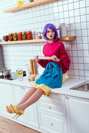 housewife with purple hair sitting on kitchen counter with rolling pin