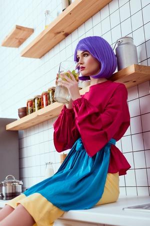 selective focus of housewife with purple hair and colorful clothes sitting on kitchen counter and holding glass jar of lemonade
