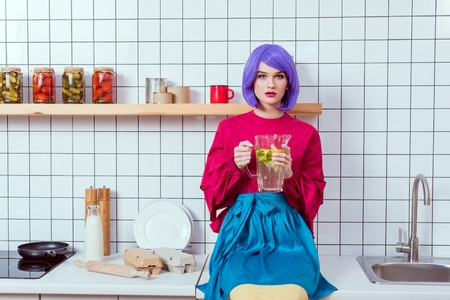 housewife with purple hair and colorful clothes sitting on kitchen counter and holding glass jar of lemonade Reklamní fotografie
