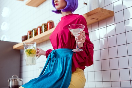 partial view of housewife with purple hair and colorful clothes holding jar of lemonade with glass in kitchen