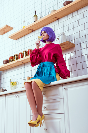 housewife with purple hair and colorful clothes sitting on kitchen counter and drinking homemade lemonade 版權商用圖片