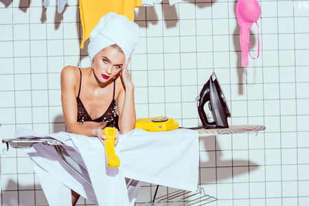 housewife in towel and lingerie looking at camera and holding retro telephone in bathroom