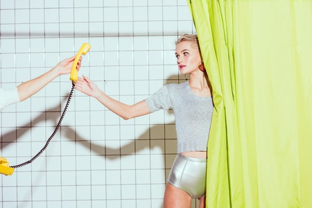 beautiful stylish woman taking yellow retro telephone handset in shower with green curtain Archivio Fotografico
