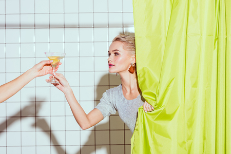 beautiful young woman behind curtain taking cocktail in shower