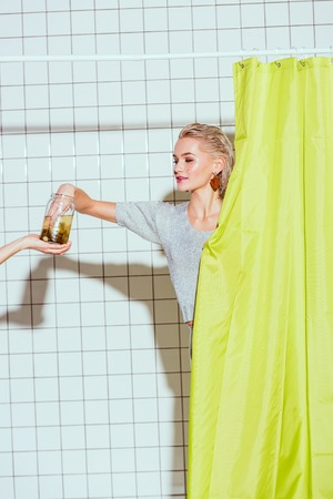 beautiful woman taking pickled cucumber from glass jar in shower