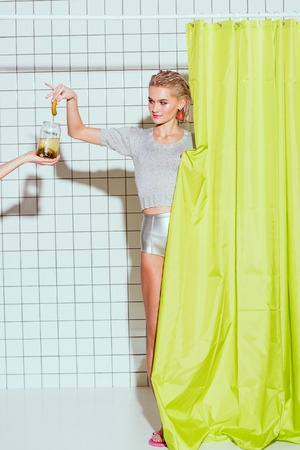beautiful young woman taking pickled cucumber from glass jar in shower