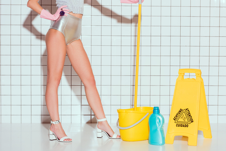 cropped view of housewife in rubber gloves with cleaning equipment in bathroom