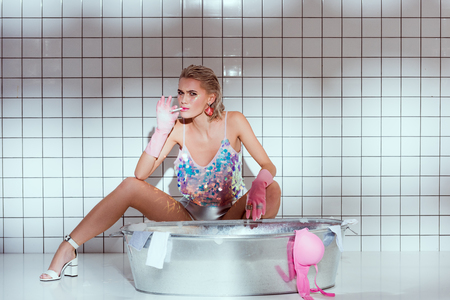 beautiful housewife in rubber gloves looking at camera and smoking while washing clothes in bathroom 免版税图像