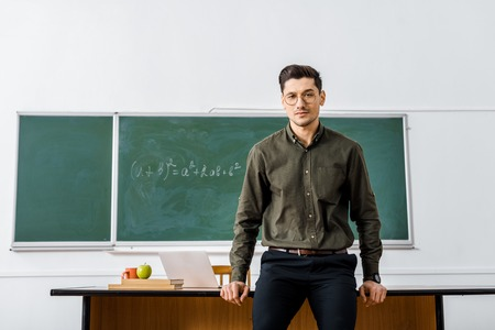 serious male teacher in formal wear looking at camera and standing near desk in classroom