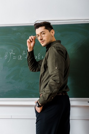 handsome male teacher holding glasses and looking at camera in maths class Stock Photo