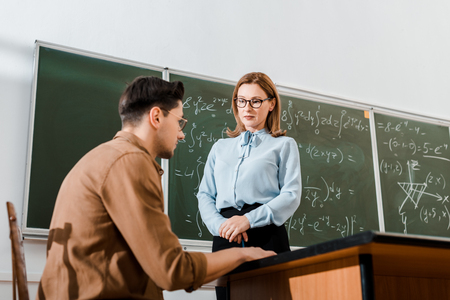 Female teacher standing in formalwear and looking at student in classroom