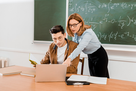 Female teacher pointing at laptop near student in class