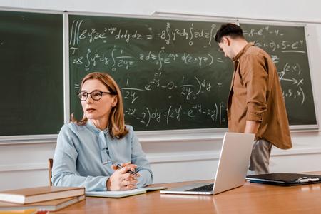 Female teacher sitting at desk near laptop while student standing near chalkboard