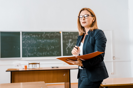 beautiful female teacher in formal wear and glasses holding notebook in classroom Foto de archivo - 118631870