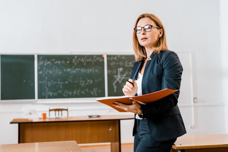 Hermosa maestra en ropa formal y gafas sosteniendo el cuaderno en el aula