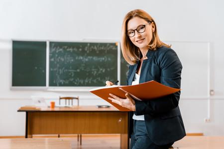 Schöne Lehrerin in formeller Kleidung, die im Notizbuch schreibt und im Klassenzimmer in die Kamera schaut