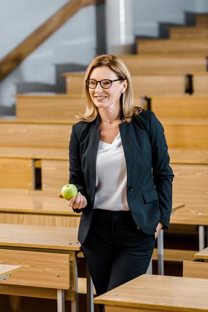smiling female teacher in formal wear holding apple in classroom 版權商用圖片