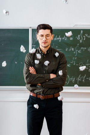 crumpled paper balls flying at male teacher with arms crossed in classroom with chalkboard on background