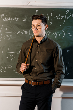serious male teacher in formal wear holding wooden pointer in front of chalkboard with equations