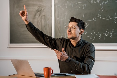 male teacher sitting at desk, pointing finger in air and explaining equations in maths classroom