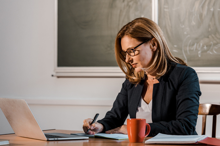 female teacher sitting at computer desk and writing in notebook during lesson in classroom