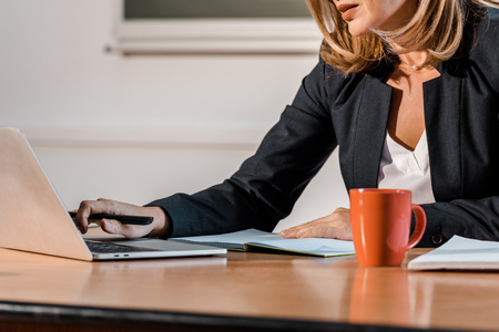 cropped view of teacher using laptop and sitting at desk Stock Photo