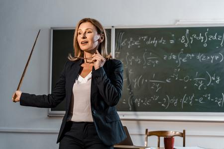 Lehrerin mit Holzzeiger, der eine Brille hält und mathematische Gleichungen im Klassenzimmer erklärt