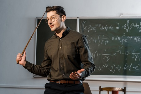 handsome male teacher in formal wear holding wooden pointer and explaining equations in class Stock Photo
