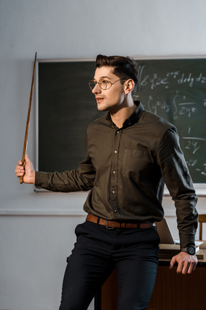male teacher in formal wear and glasses holding wooden pointer and explaining equations in class