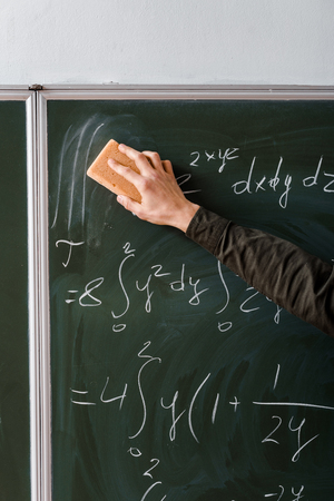 cropped view of male student wiping mathematical equations with sponge in classroom