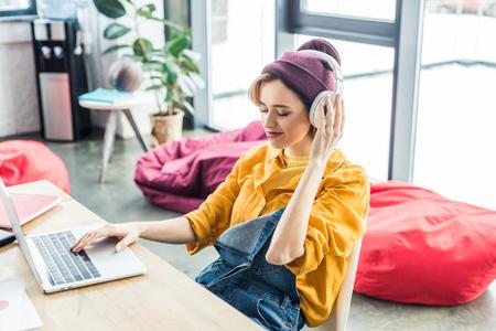 young female it specialist in headphones using laptop in loft office