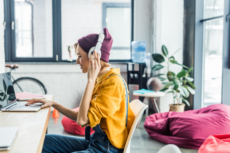 young female it specialist in headphones using laptop in loft office with copy space Stock Photo