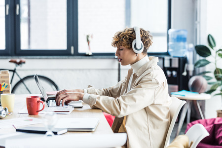 handsome it specialist in headphones sitting at desk and using laptop in loft office Stock Photo