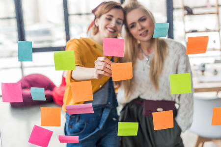 beautiful casual businesswomen colorful putting sticky notes on glass window in office 스톡 콘텐츠
