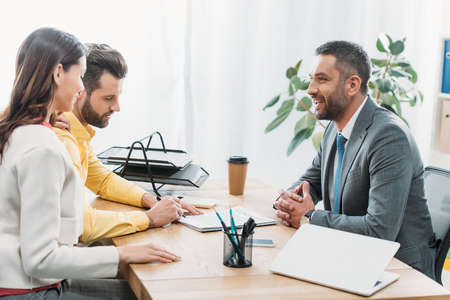 Berater und Frau, die am Tisch sitzen, während der Investor im Büro ein Dokument unterschreibt