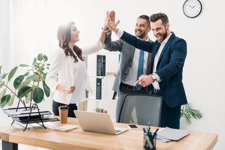 colleagues standing near table with laptop and highing five in office
