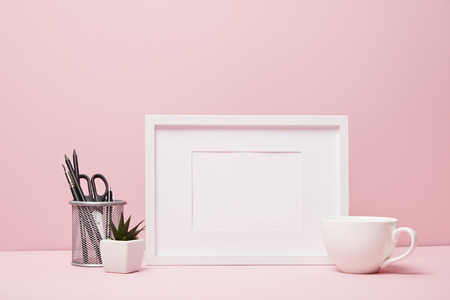 blank frame near green plant, metallic holder with stationery and cup