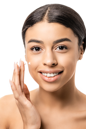 close-up view of beautiful young african american woman applying face cream and smiling at camera isolated on white
