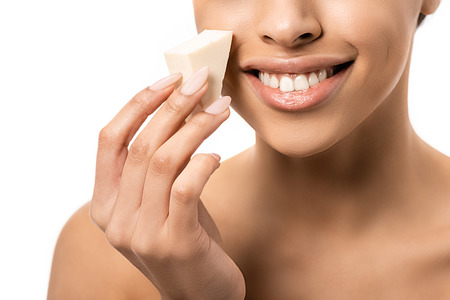 close-up partial view of smiling young african american woman holding makeup sponge isolated on white