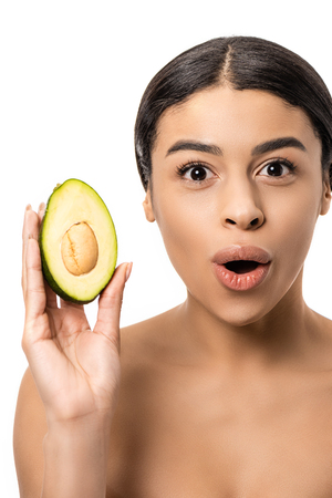 surprised young african american woman holding avocado and looking at camera isolated on white Imagens