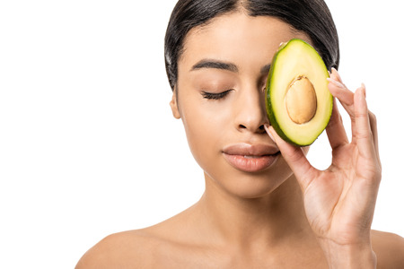 beautiful young african american woman holding half of avocado near face isolated on white