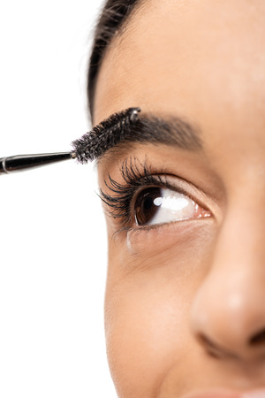 close-up view of beautiful young african american woman correcting eyebrow with brush isolated on white